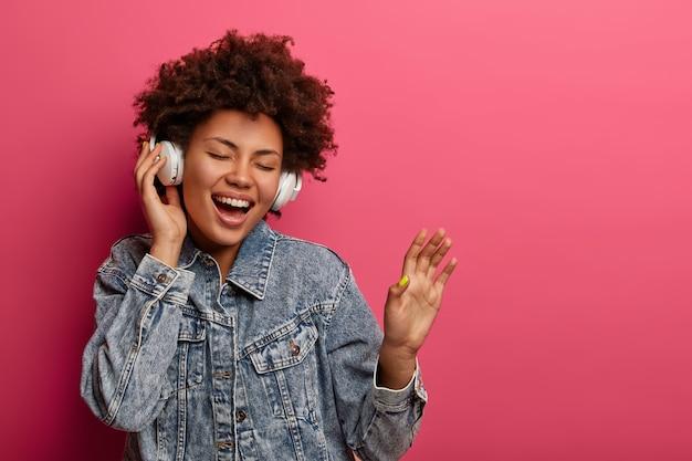 Happy ethnic female meloman raises palm, listens audio track in modern headphones