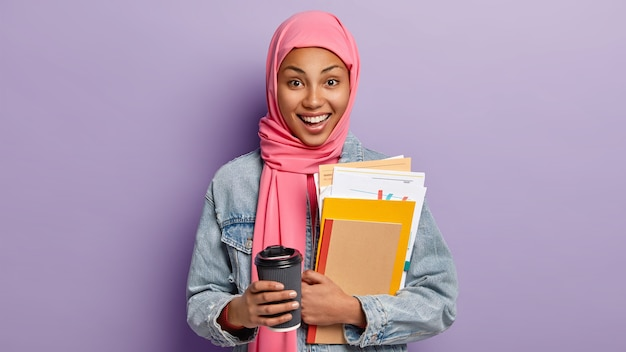 Happy ethnic female student has coffee break, holds takeaway cup of drink, carries notebook and papers, has pink scarf on head, islamic religious views, poses indoor. people, culture, tradition
