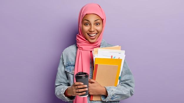 幸せな民族の女子学生はコーヒーブレイクを持ち、飲み物の持ち帰り用のカップを保持し、ノートと書類を運び、頭にピンクのスカーフを持ち、イスラム教の宗教的な景色を眺め、屋内でポーズをとります。人、文化、伝統