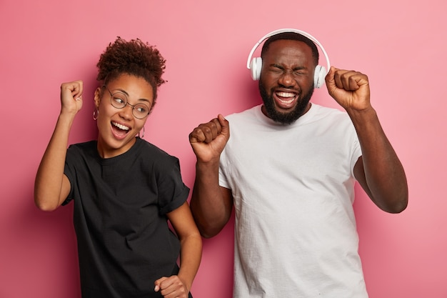 Happy ethnic girlfriend and boyfriend enjoy music in headphones, dance happily, clench fists, dressed in casual t shirts, laugh joyfully, isolated on pink wall.