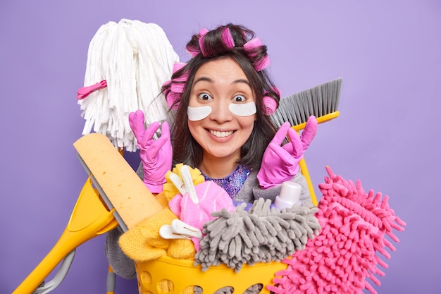 Happy ethnic housewife raises hands smiles broadly uses cleaning products and housekeeping equipment applies pads under eyes makes hairstyle isolated over purple background. household concept