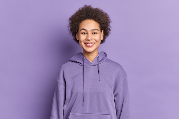 Happy ethnic teenager with afro hair smiles positively wears purple hoodie being in good mood.