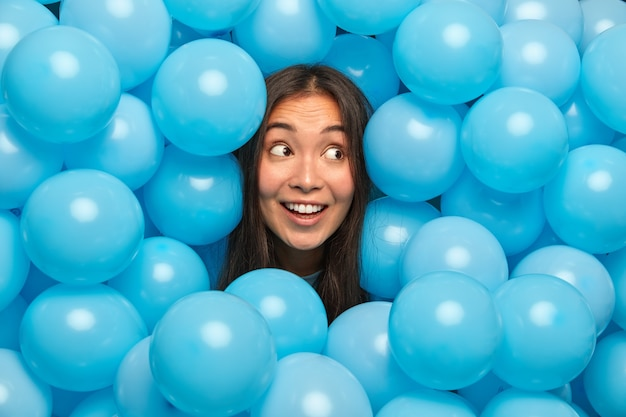 Happy ethnic woman looks mysteriously aside and broad smile poses against blue balloons awaits for special event.