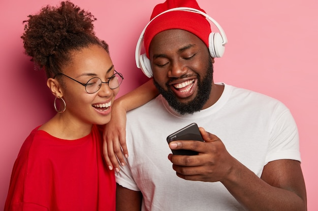 Happy ethnic woman and man watch funny video on smartphone, black man in red hat and white t shirt, wears headphones, shows new app to girlfriend