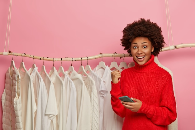 Happy ethnic woman rejoices getting free gift with purchase in clothes shop, holds cellular and clenches fist, wears red sweater, poses near rack with white clothing.