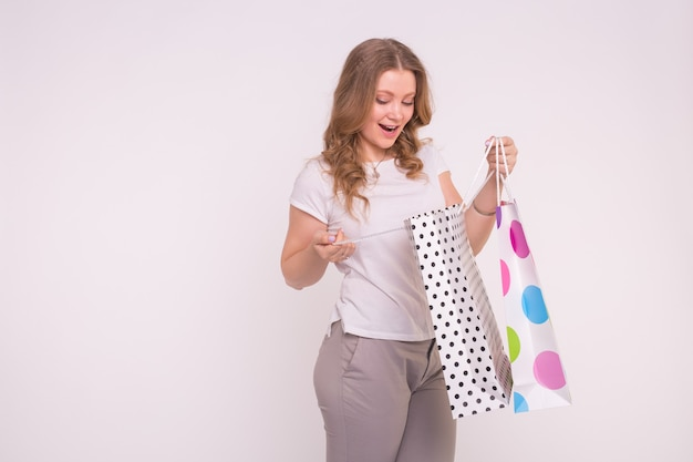 Happy european blond girl with coloured shopping bags on white surface with copy space