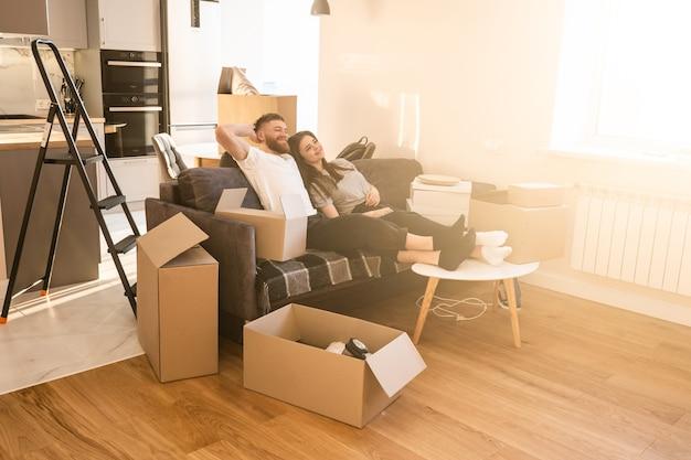 Счастливая европейская пара сидит и отдыхает на диване у себя дома. концепция переезда в новую квартиру. идея молодой семьи. картонные коробки с вещами. интерьер однокомнатной квартиры. солнечный день