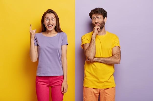 幸せなヨーロッパの黒髪の女性は、カジュアルな服を着て、上に人差し指を指し、思慮深い無精ひげを生やした男は彼女を見て、彼女の推薦を聞き、提案に同意せず、あごを保持します