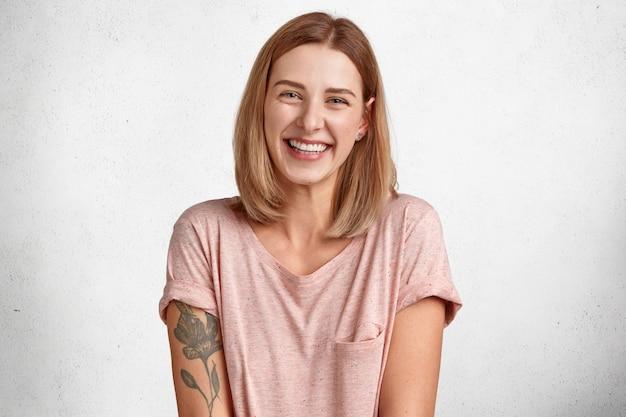행복한 유럽 여성은 즐겁게 웃고, 하얀 치아를 보여주고, 단발 머리 헤어 스타일, 캐주얼 티셔츠를 입고, 문신을하고, 고립되어 있고, 즐거운 칭찬을받습니다. 감정.