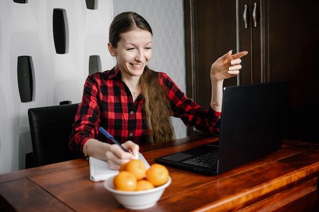 ノートパソコンを使用しながら笑顔、カジュアルな服装で幸せなヨーロッパの女子学生