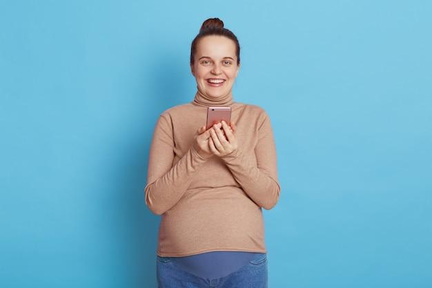 Счастливая европейская женщина в бежевом свитере и джинсах с пучком для волос с помощью мобильного телефона на синем