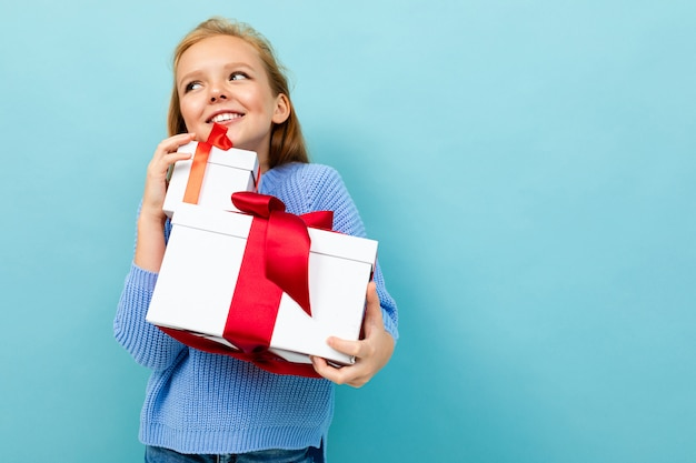 Happy european girl holding a gift on a light blue  with copyspace