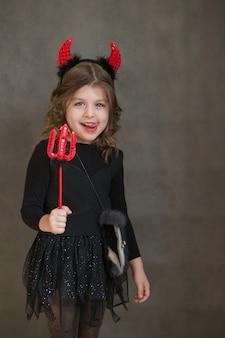 Счастливая европейская девушка в чёртовом костюме хэллоуина