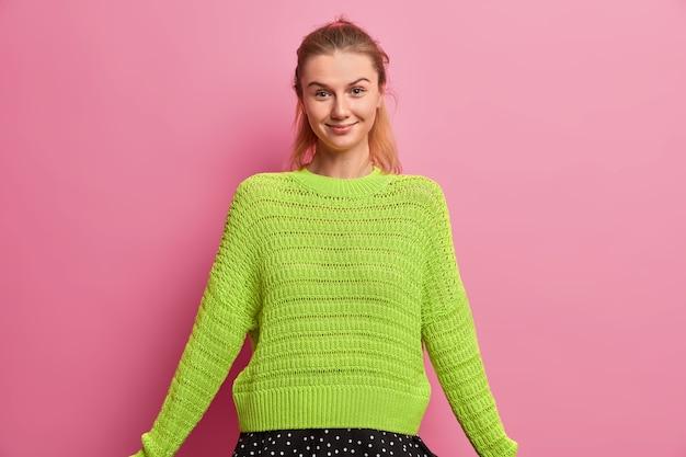 特大のニットセーターを着た幸せなヨーロッパの女の子は、心地よく笑顔で、自信を持って表情を見せ、誠実な表情をしています