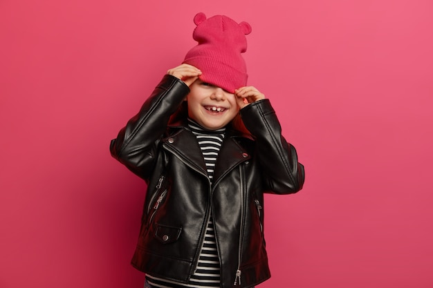 Happy european girl wears pink hat with ears, black leather jacket, hides herself when mother tries to make photo of her, has joyful expression, poses over pink vibrant wall. style and childhood
