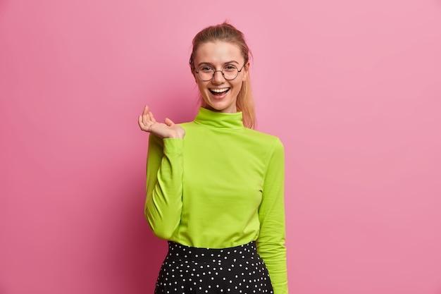 쾌활한 표정으로 행복한 유럽 소녀, 재미있는 것을 웃고, 친구 서클에서 자유 시간을 보내고, 캐주얼 한 녹색 터틀넥을 입은 황홀감을 느낍니다. 사람, 감정, 라이프 스타일