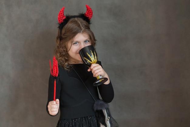Счастливая европейская маленькая девочка в чертовом костюме хэллоуина