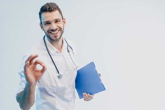 Счастливый европейский мужской доктор держит доску сзажимом для бумаги и показывая одобренный жест. молодой бородатый человек со стетоскопом в белом халате. изолированные на сером фоне с бирюзовым светом. студийная съемка. скопируйте пространство.
