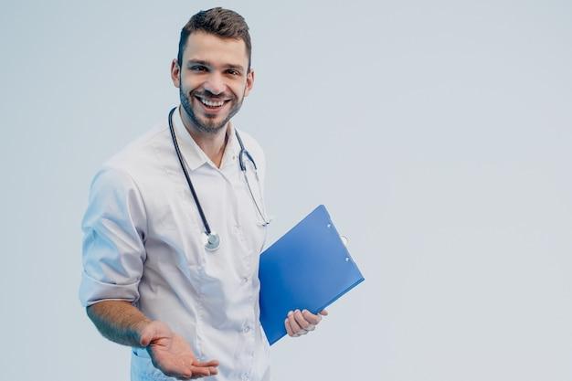 Счастливый европейский мужской доктор держать доску сзажимом для бумаги. молодой бородатый человек со стетоскопом в белом халате. изолированные на сером фоне с бирюзовым светом. студийная съемка. скопируйте пространство.