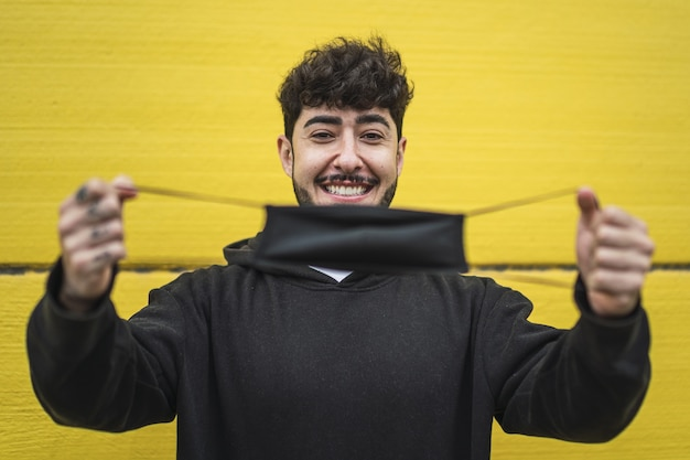 Happy european male showing a face mask on vibrant yellow wall
