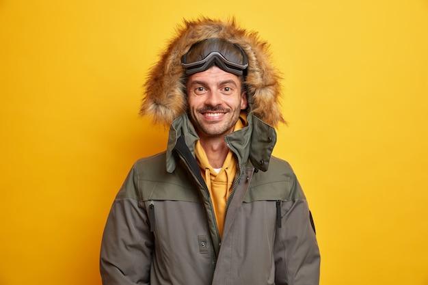 毛皮のフード付きのジャケットを着た幸せなヨーロッパ人は、冬の間は暖かく快適に感じ、好きな季節の笑顔を楽しんでいます。スケートボードのゴーグルを着て幸せに休んでいます。
