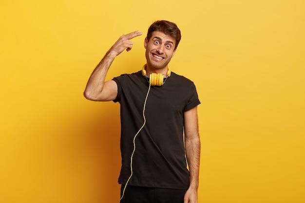 행복한 유럽 남자는 성전에서 촬영하고, 캐주얼 한 검은 색 티셔츠를 입고, 목에 헤드폰을 쓰고, 머리를 기울입니다.
