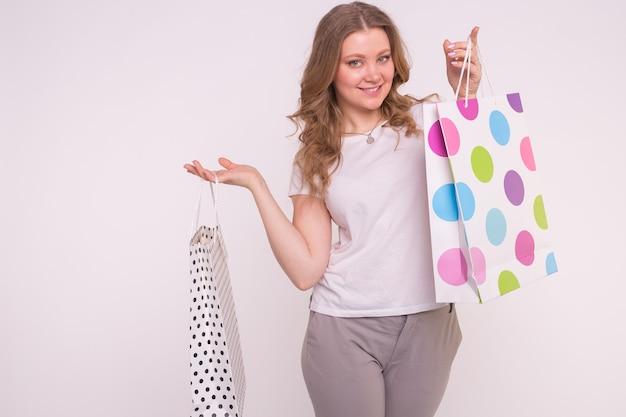 Счастливая европейская женщина большого размера, держащая хозяйственные сумки на белой стене.