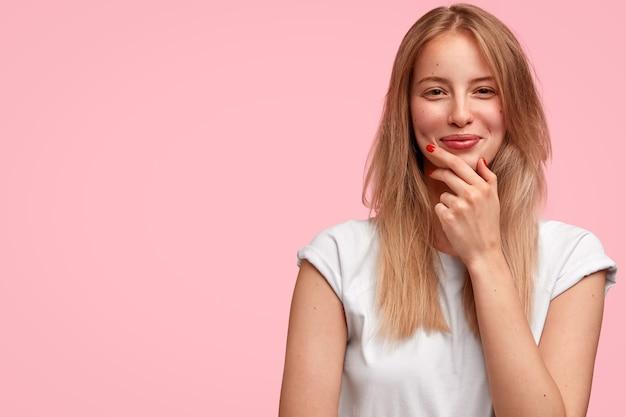 幸せなヨーロッパの女性はあごを持って、前向きに見え、カジュアルな服を着て、友人から楽しい話を聞きます