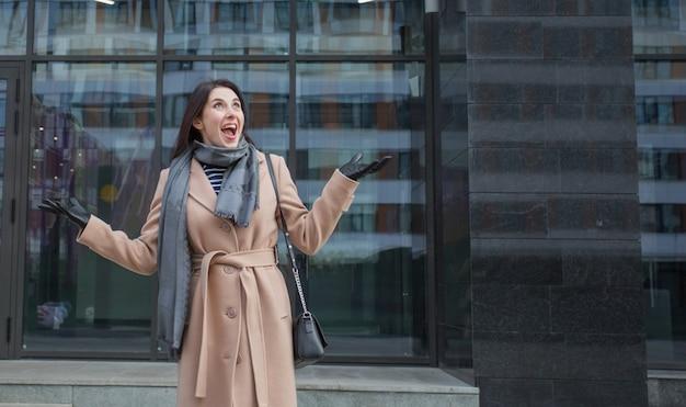 秋の街に立っているコートを着た幸せなヨーロッパの女性