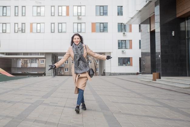 秋の街を歩いているコートを着た幸せなヨーロッパの女性。高品質の写真