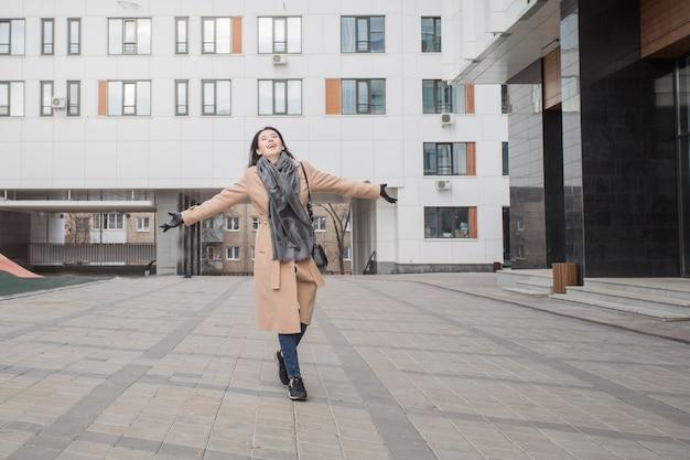 秋の街を歩いているコートを着た幸せなヨーロッパの女性
