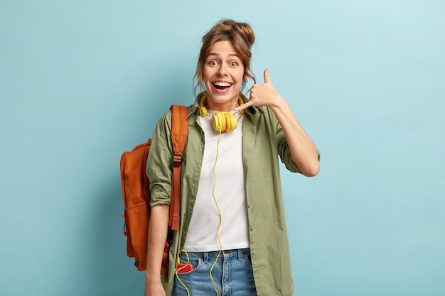 행복한 유럽 여성이 전화 제스처를 만들고 거리에서 친구와 연락을 시도하며 현대적인 헤드폰을 착용합니다.