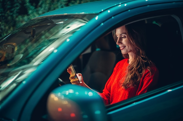 Happy european woman sit in car and use smartphone