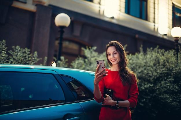 幸せなヨーロッパの女性が車の近くにスマートフォンを使用します