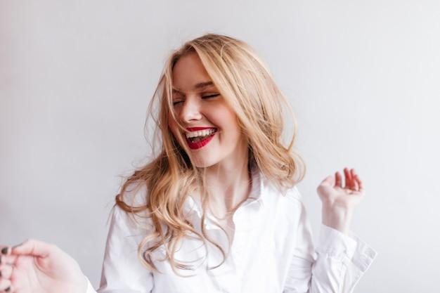Felice donna europea in camicia bianca che esprime emozioni positive. gioiosa ragazza bionda sulla parete chiara.