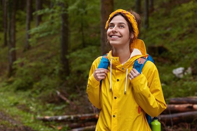 Felice donna europea con espressione felice, guarda in alto, di buon umore, respira l'aria fresca della foresta