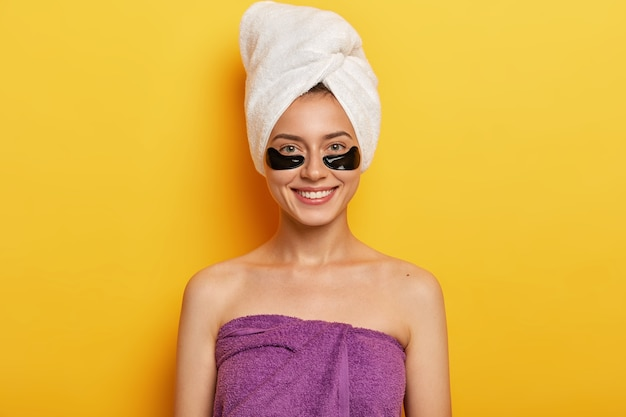 Happy european woman with gentle smile, has black collagen patches, reduces problem of dark circles under eyes, wrapped in towel on head and over body, improves skin condition