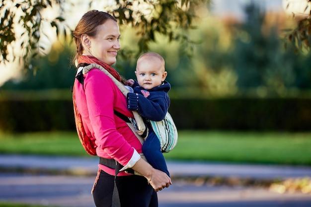 Счастливая европейская женщина с маленьким мальчиком в слинге гуляет в парке