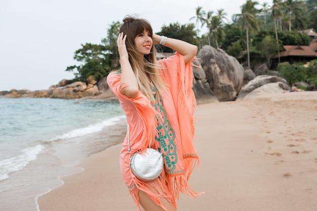 Счастливая европейская женщина с длинными волосами в стильном летнем платье бохо позирует на тропическом пляже.