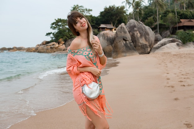 Felice donna europea con i capelli lunghi in elegante abito estivo boho in posa sulla spiaggia tropicale.