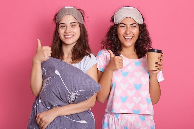 Happy european women standing with satisfied facial expressions, having fun together, posing in sleeping mask and pajamas, holding coffee in disposable cup, show thumb up, wake up with good mood.