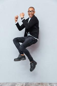 幸せな興奮したアフリカ系アメリカ人の若い男がジャンプして成功を祝う