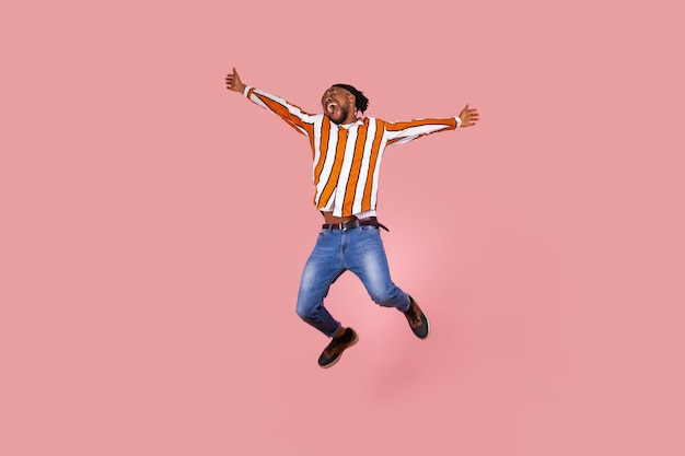 Happy excited afro-american man highly jumping widely opening hands and screaming feeling freedom