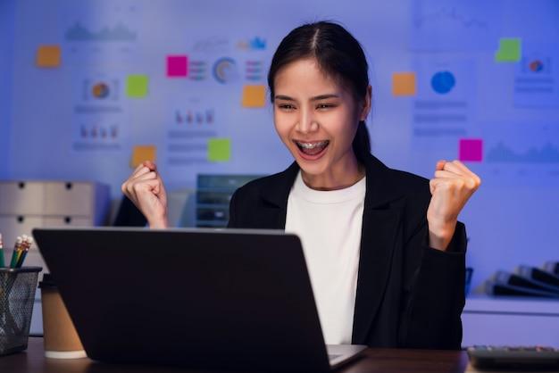 Счастливый взволнованный азиатский бизнес-леди празднует успех и работает на ноутбуке на столе в ночное время.
