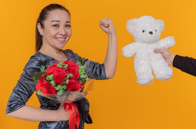 Happy and excited asian woman looking receiving teddy bear as a gift smiling cheerfully clenching fist celebrating international women's day standing over orange wall