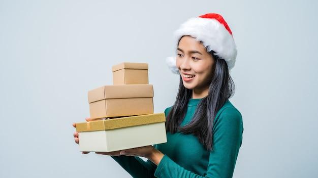 クリスマスシーズンのギフトボックスを保持しているサンタクロースの帽子を持つ幸せな興奮したアジアの女性。