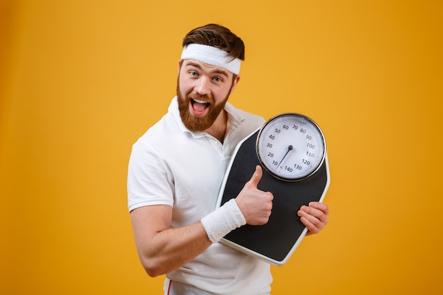 Happy excited bearded fitness man holding weight scales