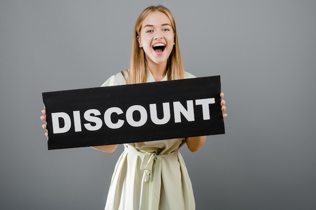 Happy excited beautiful girl has discount sign isolated over grey