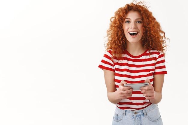 Счастливая возбужденная красивая рыжая кудрявая девушка веселится, играя в потрясающую игру для смартфона, держа мобильный телефон горизонтальный взгляд камеры, игриво ухмыляясь проверить новое крутое приложение обожаю