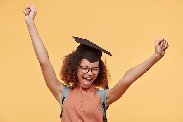 Happy excited black graduate student in eyeglasses and academic cap raising arms and screaming after completing her degree